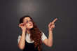 young curly woman in glasses pointing at empty copyspace