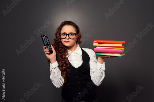 woman in glasses choosing between tv and books