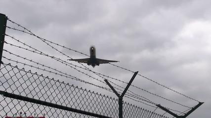 Flugzeug im Landeanflug überfliegt Stacheldraht - Zeitlupe