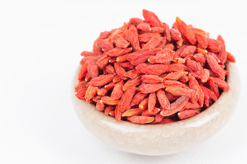 dried wolfberry fruit in bowl on white background