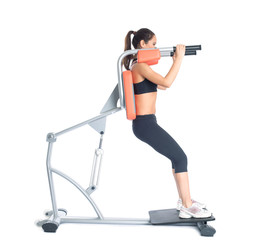 Beautiful slim woman trains on exerciser