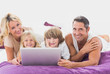 Smiling family using laptop