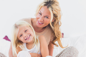 Mother and her daughter sitting on a bed