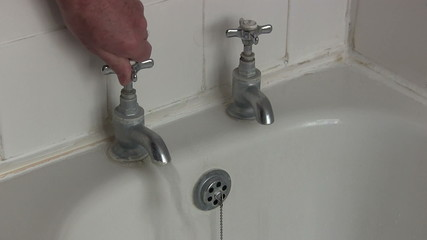Hot and cold bath taps being turned on.