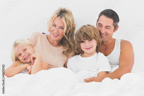 Family lying on a white bed