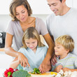 Mother teaching daughter to slice vegetables as father and son a