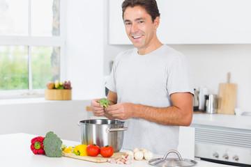 Smiling man making dinner