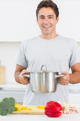 Man holding large pot in front of chopping board with vegetables