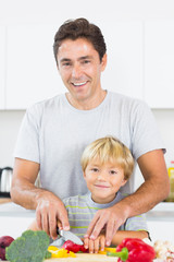 Father showing son how to slice vegtables