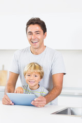 Laughing father and son using tablet