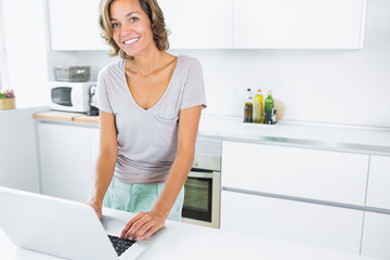 Pretty woman in kitchen with laptop