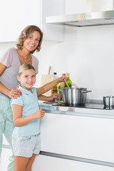 Happy mother and daughter cooking together