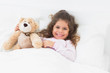 Little girl in bed with teddy bear