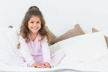 Cute girl sitting on bed