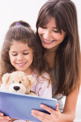 Happy mother and daughter using tablet pc