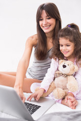 Mother and daughter using laptop with teddy bear