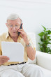 Elderly focused man reading papers on the phone
