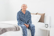 Aged man sitting on his bed