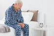 Elderly man sitting on the bed