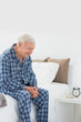 Calm elderly man sitting on the bed