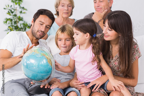 Happy family looking at globe