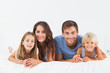 Smiling family lying on a bed