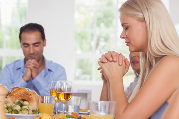 Woman saying grace with family before dinner