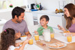 Family laughing around breakfast
