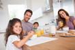 Family smiling at the camera at breakfast