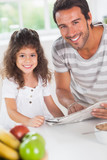 Dad and daughter reading a newspaper during breakfast