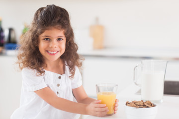 Cute girl smiling with her orange juice in hand