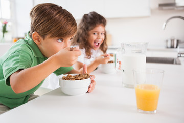 A little boy and a little girl eating cereal