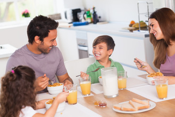 Family laughing around breakfast