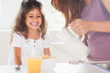 Mother putting milk in the cereal of his daughter