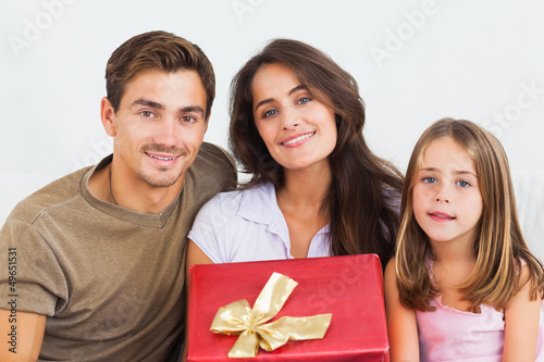 Father and his daughter offering a gift to her mother