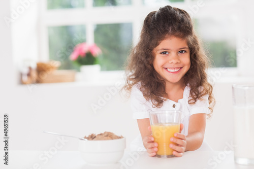 Little girl smiling with her orange juice in hand