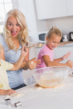 Mother making a face while her children take care of the dough