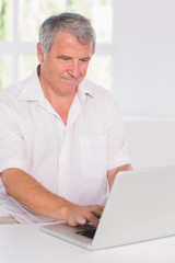 Old man concentrating in front of his laptop
