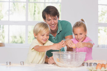 Children breaking eggs into a bowl