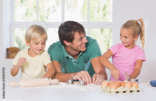Father and his children cutting cookies out