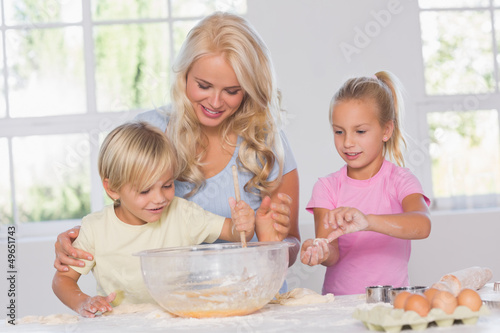 Children mixing dough with their mother