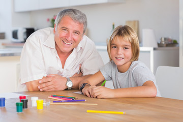 Grandfather and grandson looking at camera with drawings