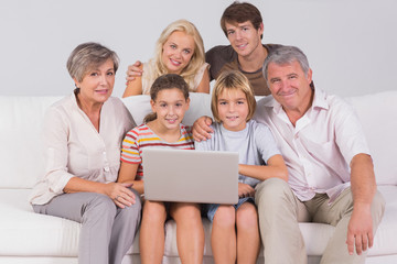 Family portrait looking at camera with a laptop