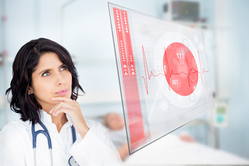 Doctor looking up at screen showing red ECG data