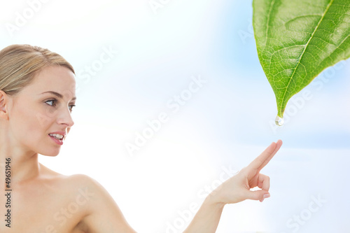 Blonde reaching out to dew drop falling from leaf