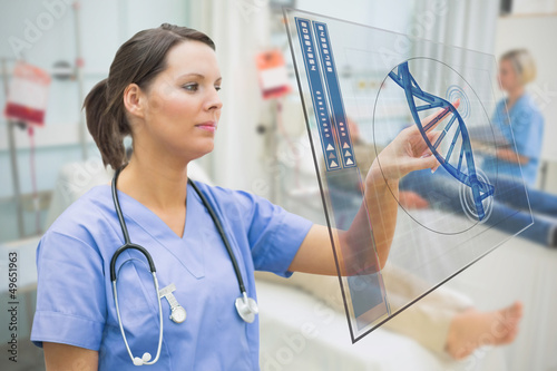 Nurse touching screen displaying blue DNA helix data