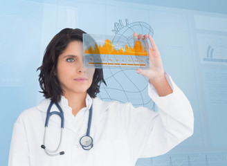 Brunette doctor looking at a graph with futuristic technology