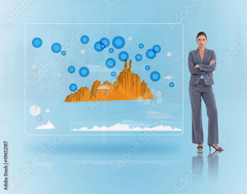 Serious businesswoman standing near to a futuristic screen