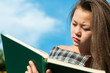 young asian girl reading outdoor