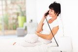 pretty middle aged woman talking on landline phone on bed